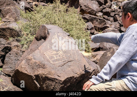 A boy pointing at petroglyphs at Petroglyph National Monument, New Mexico, United States - Stock Photo