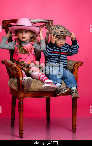 two children smiling wearing cowboy hats, Studio - Stock Photo
