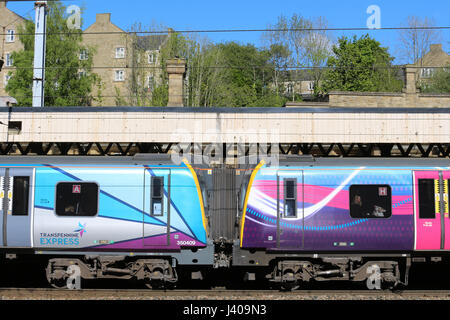 Old and new First Transpennine Express liveries on two class 350 electric trains in platform 4 at Lancaster railway - Stock Photo