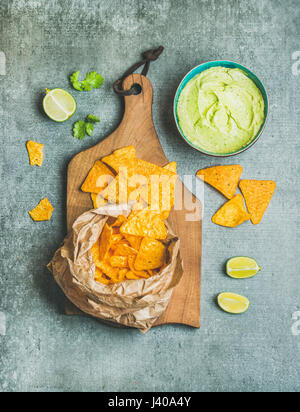Mexican corn chips and fresh guacamole sauce on wooden board - Stock Photo