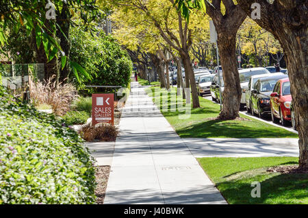 Los Angeles, USA - March 9, 2014: Sidewalk on street in downtown LA in Beverly Hills with residential houses and - Stock Photo