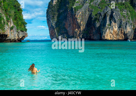 Scenic View of Woman by Sea Against Rock formations - Stock Photo