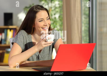 Happy woman with a laptop holding a cup of coffee relaxing and thinking looking through a window at home - Stock Photo