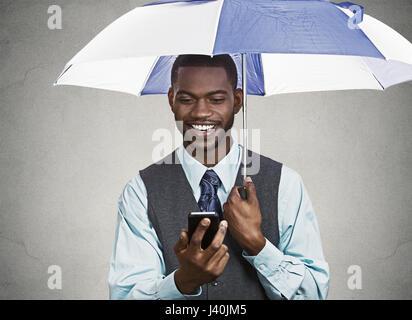 Closeup portrait happy, smiling corporate business man, executive reading message news on smart phone holding umbrella, - Stock Photo