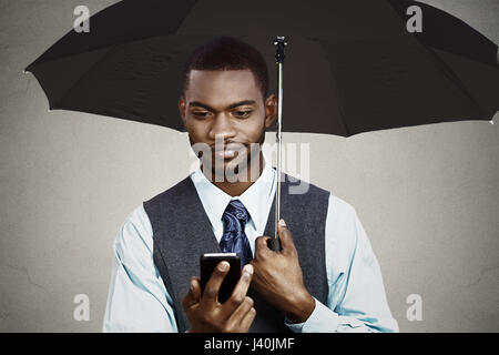 Closeup portrait skeptical business man reading bad news on smart, mobile phone holding umbrella protected from - Stock Photo