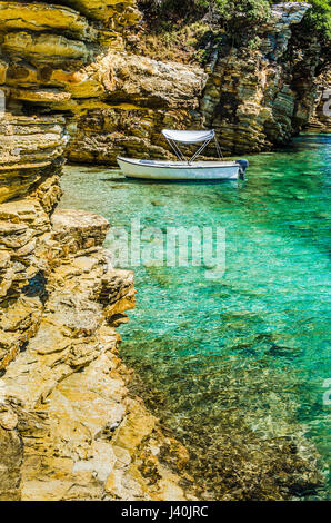 White boat in small cute azure bay surrounded by lime stone cliffs in Corfu island, Greece - Stock Photo