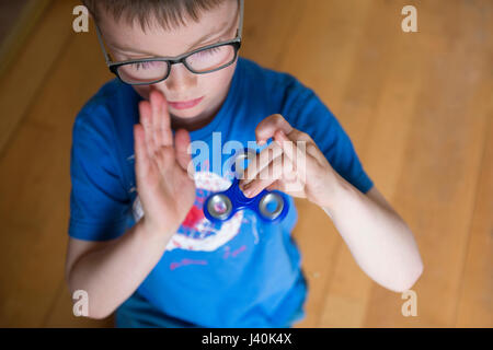 A closeup crop of a young boy spinning his blue fidget spinner which is the new toy craze invented by catherine - Stock Photo