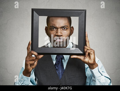 Closeup portrait businessman executive looking curious surprised confused skeptical through black picture frame - Stock Photo