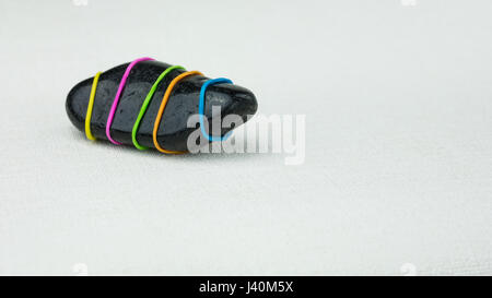 Being different one black stone with coloured stripes on bright background