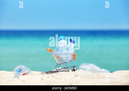 Miniature shopping cart with empty plastic bottles left by tourist on a tropical beach, environmental pollution - Stock Photo
