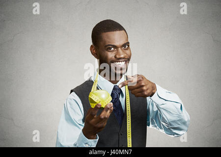 Closeup portrait headshot business man, corporate executive holding, pointing at green apple measuring tape on neck - Stock Photo