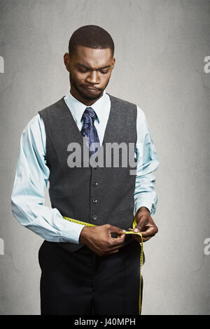 Closeup portrait skeptical, unhappy businessman, measuring waist with tape, unsatisfied with results isolated black - Stock Photo