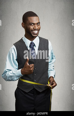 Closeup portrait smiling fitness man, excited about weight loss, measuring waist with tape, smiling, satisfied with - Stock Photo