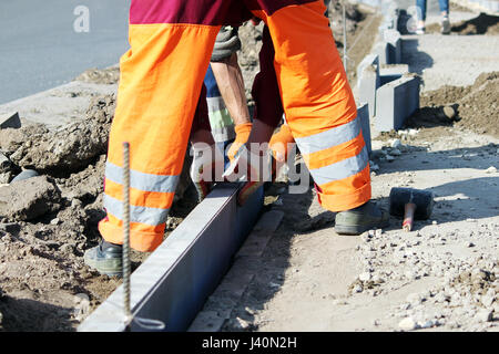 Repair of the sidewalk. Professional working masons in overalls lay curbs before laying stone paving slabs. - Stock Photo