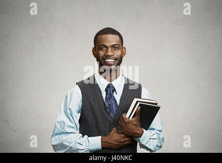 Closeup young smart, happy, smiling handsome man holding books, prepared, ready to ace his exam test finals, isolated - Stock Photo