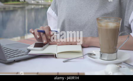 Close-up of woman working on smartphone and laptop near pool. Female work on mobile phone. Business online. Hot - Stock Photo