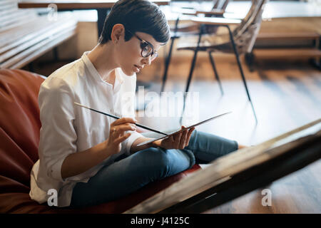 Creative pensive art school painter working on painting project - Stock Photo
