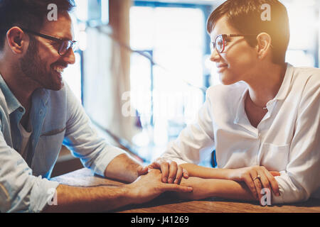 Young couple in love holding hands, looking at each other and smiling while sitting at cafe - Stock Photo