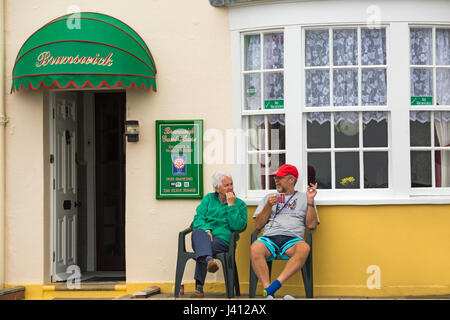 Couple sitting outside the Brunswick Guest House relaxing and having a cuppa at Weymouth, Dorset in May - Stock Photo