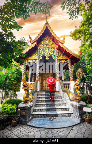 Woman tourist with red traditional Thai umbrella in the temple monastery with dragon statues at sunset sky in Chiang - Stock Photo