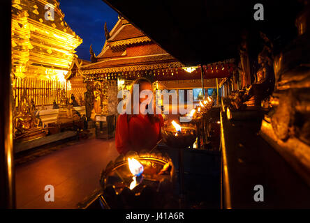 Woman tourist looking at prayer candle lights at Buddhist Temple Doi Suthep at night in Chiang Mai, Thailand - Stock Photo