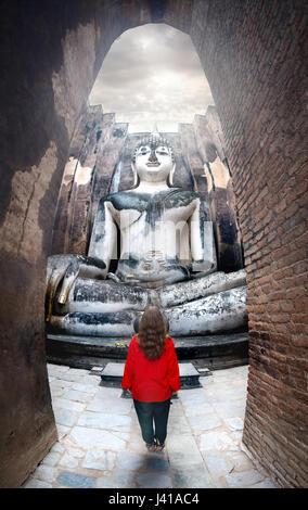 Woman in red shirt standing near giant statue of Buddha call Phra Achana in Wat Si Chum in Sukhothai Historical - Stock Photo