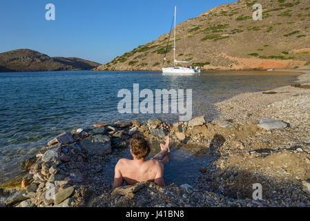 A young man lying in a hot pool on the beach of a lonely bay on the greek island Kithnos, Kolona, Aegean, Cyclades, - Stock Photo