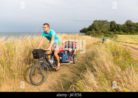 Cyclist with child trailer cycling along coastal path, Naesgaard, Falster, Denmark - Stock Photo