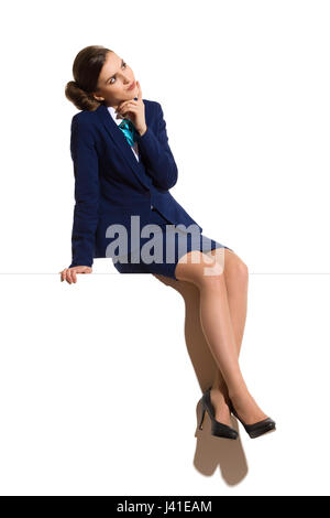 Young woman in blue formal businesswear and black high heels, sitting on a top with legs crossed, thinking and looking - Stock Photo