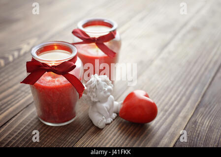 Statuette of small angel with stone heart and candles over wooden background - Stock Photo