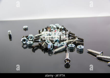 Heap of bolts, screws and nuts on neutral background - Stock Photo