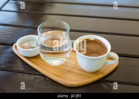 Turkish coffee on the wood with glass of water and turkish delights - Stock Photo