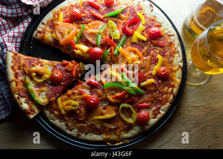 View from above of a vegetable pizza with some beer - Stock Photo