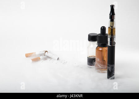 Electronic cigarette with 2 e-liquids and pile of broken tobacco smokes - Stock Photo