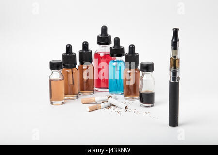 Many bottles of e-juice and vaporizer and pile of tobacco cigarettes - Stock Photo