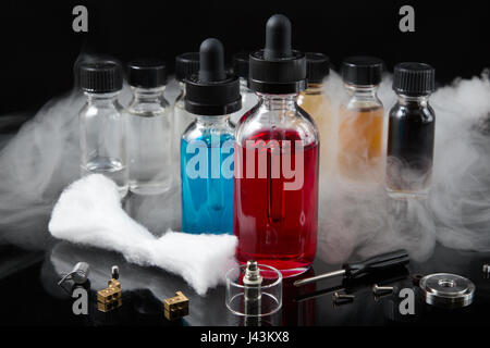 Vaporizer smoke with juice bottles, screwdriver and cotton wick with tools - Stock Photo