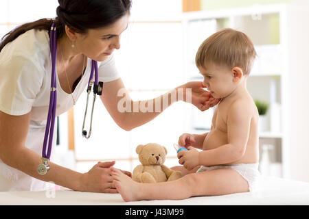 Doctor paediatrician checking boy's neck - Stock Photo