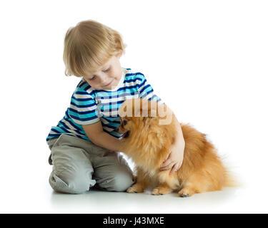 Kid boy hugging dog spitz isolated on white background - Stock Photo