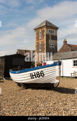An old traditional fishing boat IH86 parked on the shingle beach in front of the old lifeboat station  at Aldeburgh - Stock Photo