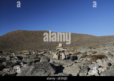 An ancient Inuit inukshuk (inuksuk) located near Qikiqtarjuaq as part of landmarks on a hiking trail, Broughton - Stock Photo