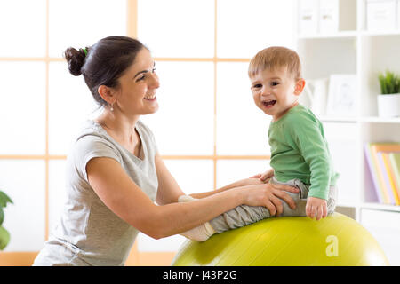 Happy mother with baby son doing gymnastics on the big fitness ball in the gym. - Stock Photo