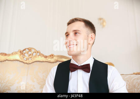 Groom sitting on the sofa waiting for the bride on his wedding day. at wedding tuxedo smiling and waiting for bride.Elegant - Stock Photo