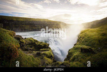 Cold water in Iceland. Waterfall in rocky mountains. Fresh and green grass. Beautiful mountain range in the background. - Stock Photo