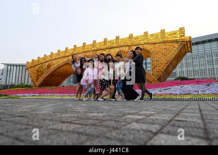 Beijing, China. 9th May, 2017. Tourists pose with the 'Golden Bridge on Silk Road' structure in Beijing Olympic - Stock Photo
