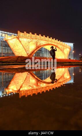 Beijing, China. 9th May, 2017. A tourist takes selfies with the 'Golden Bridge on Silk Road' structure outside the - Stock Photo