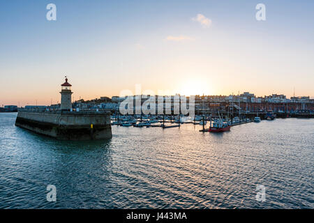 Ramsgate Royal Harbour. Lighthouse at end of jetty with boats moored in the harbour and behind that Ramsgate seafront - Stock Photo