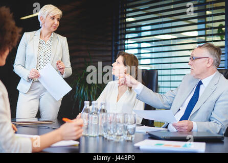 Mature woman listening to coworkers concepts - Stock Photo
