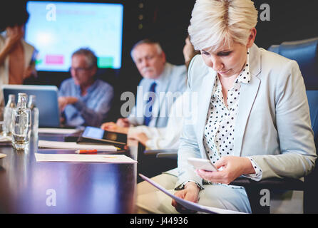 Mature woman taking picture of documents at work - Stock Photo