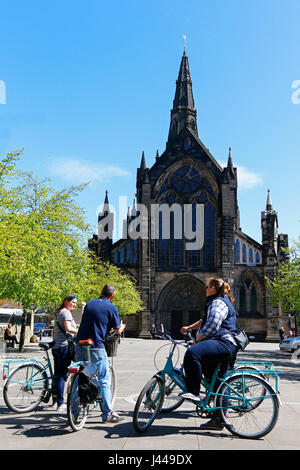 Tourists on an official city cycling tour, stopping outside Glasgow Cathedral in cathedral Square and being given - Stock Photo