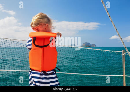 Happy little baby in life jacket on board of sailing boat watching offshore sea and tropical islands on summer cruise. - Stock Photo